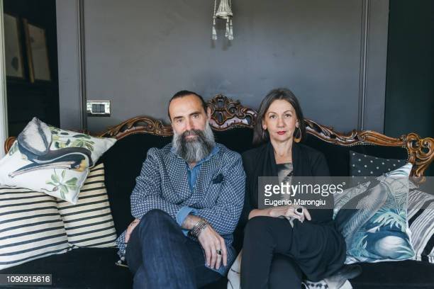 couple sitting on antique sofa - side by side stock photos and pictures