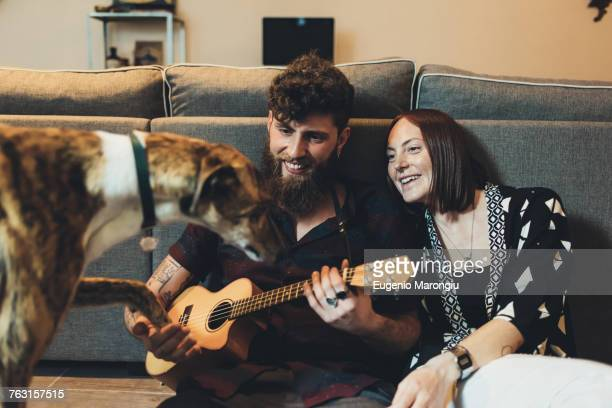 Couple sitting on apartment floor holding dogs paw