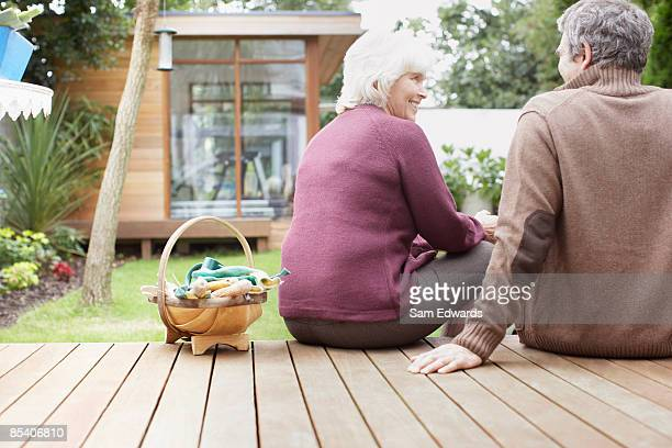 Couple sitting on backyard deck