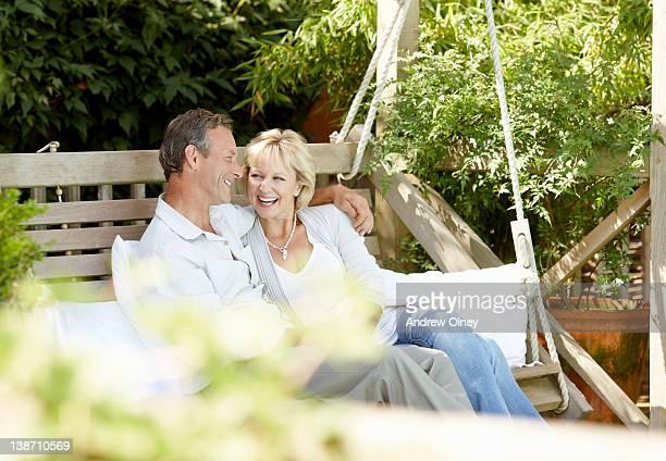 Couple sitting on backyard swing together