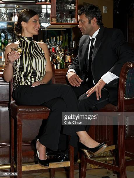 Couple sitting on barstools, talking and drinking, full length