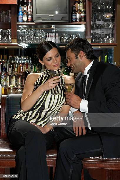 Couple sitting on barstools, toasting cocktails