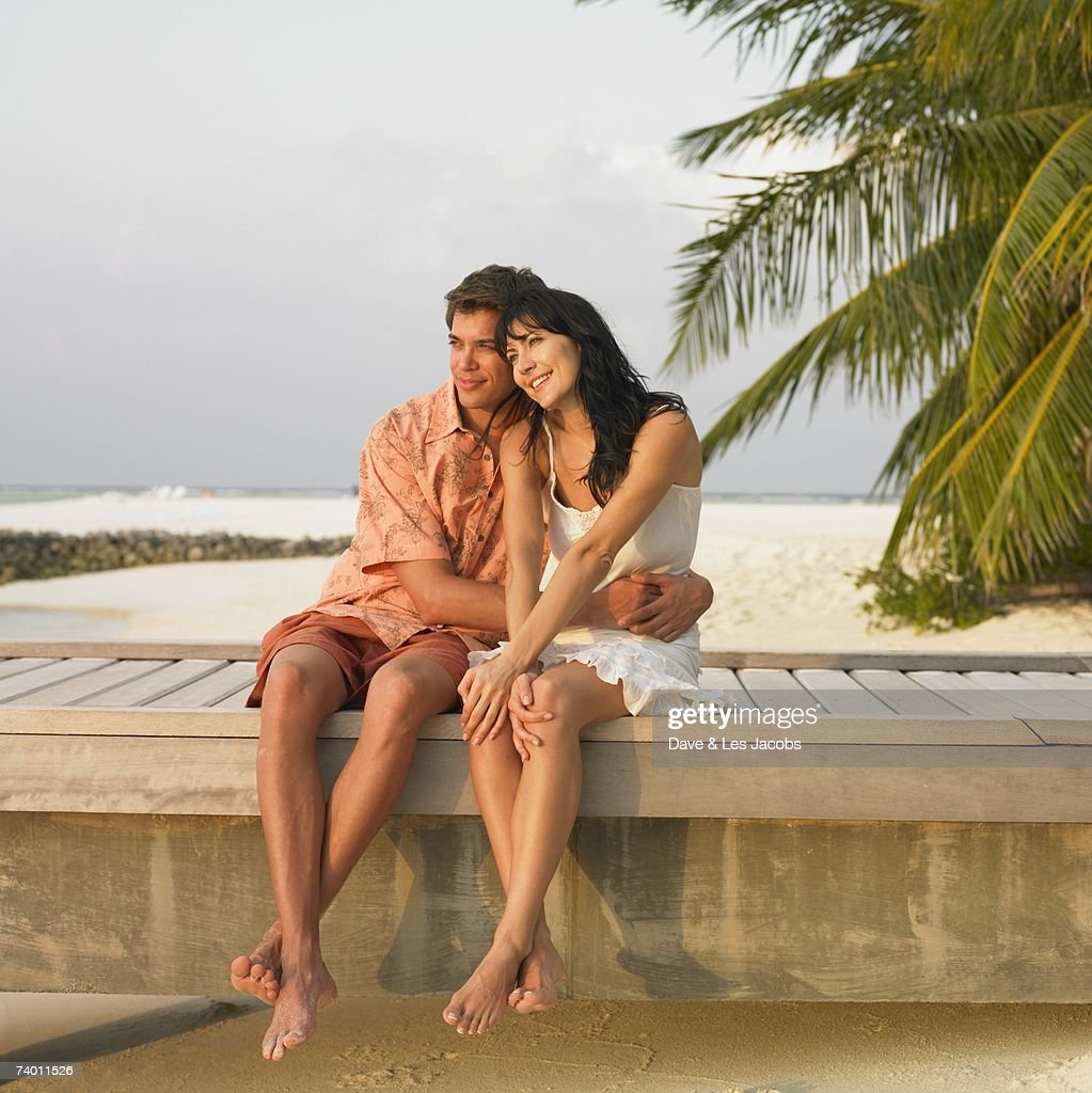Couple sitting on beach boardwalk : Bildbanksbilder