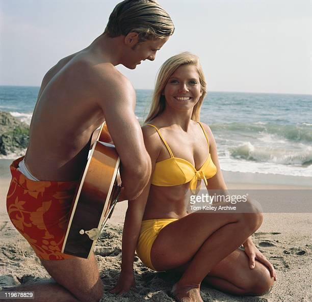 Couple assis sur la plage, homme plucking guitare