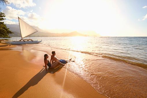 Couple sitting on beach near sailboat - gettyimageskorea