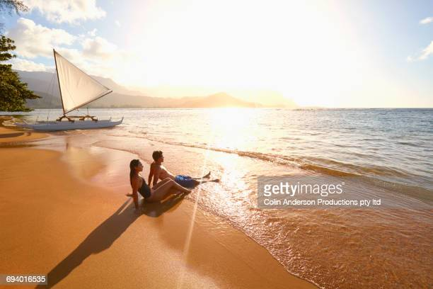 Couple sitting on beach near sailboat