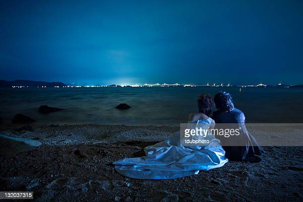 couple sitting on beach under moon - moonlight stock pictures, royalty-free photos & images