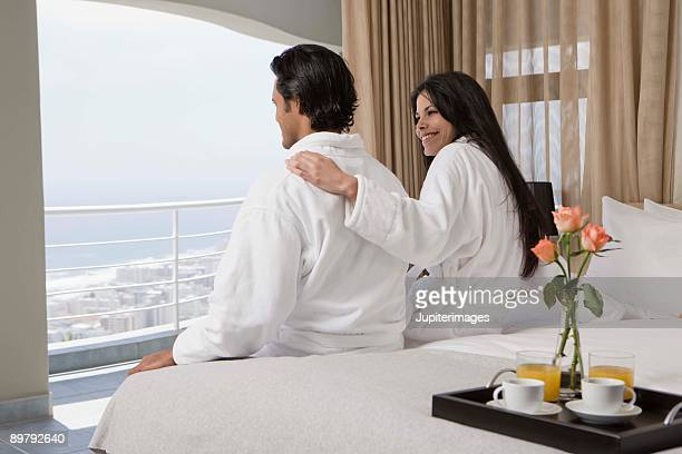 Couple sitting on bed and looking out window of hotel room