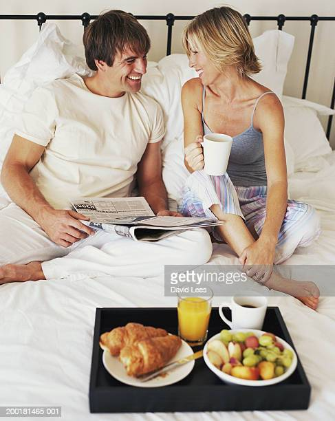 Couple sitting on bed by breakfast tray, smiling