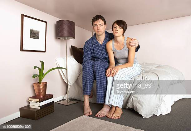 Couple sitting on bed in miniature bedroom, portrait