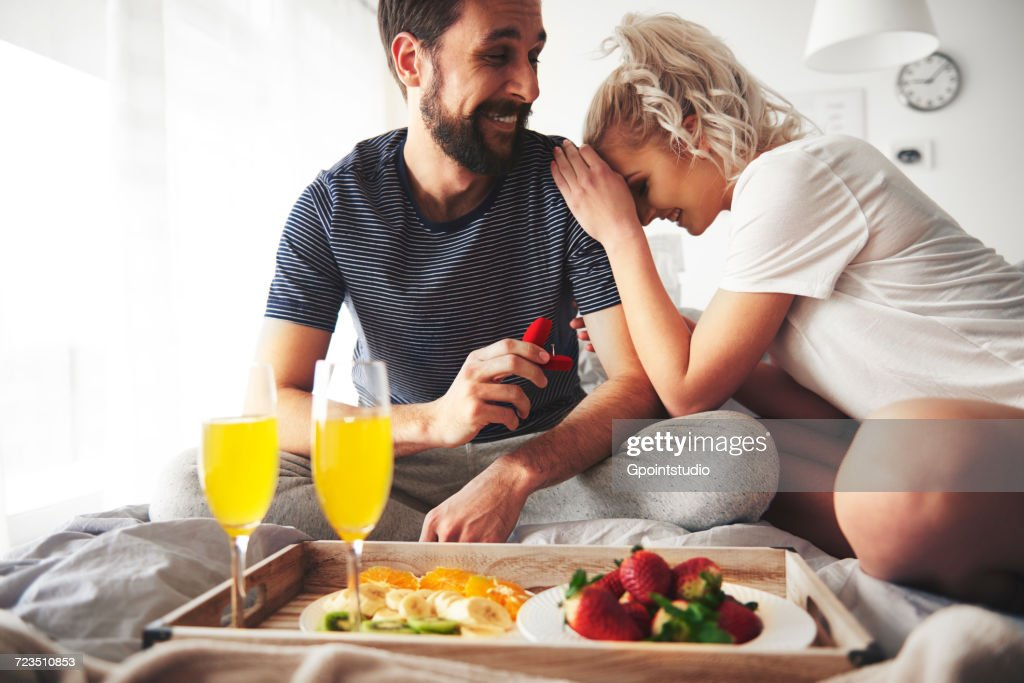 Couple sitting on bed, man proposing, holding open ring box : Stock Photo
