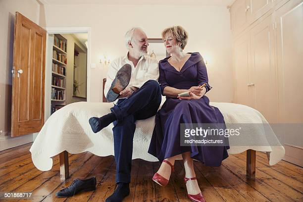 couple sitting on bed, man putting on shoes - purple shoe stock pictures, royalty-free photos & images