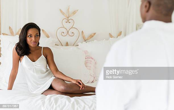 couple sitting on bed - women in slips stock photos and pictures