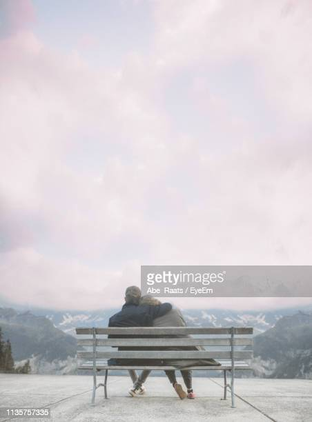 Couple Sitting On Bench Against Cloudy Sky
