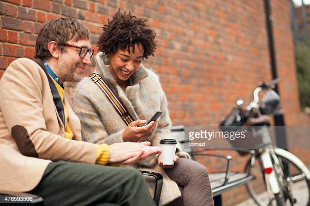 Couple sitting on bench and looking at mobile phone