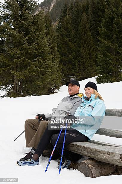 Couple sitting on bench in snow