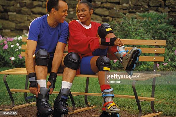 Couple sitting on bench putting on inline skates
