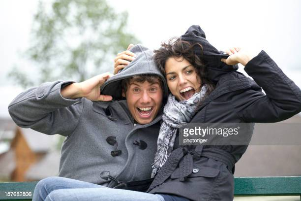couple assis sur un banc tout commence à jets de pluie