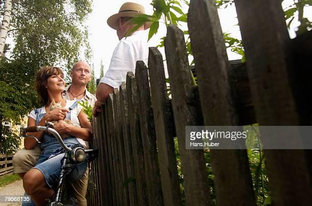 'Couple sitting on bicycle, talking to neighbor'