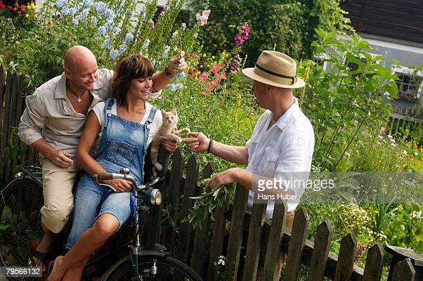 'Couple sitting on bicycle, talking to neighbor'