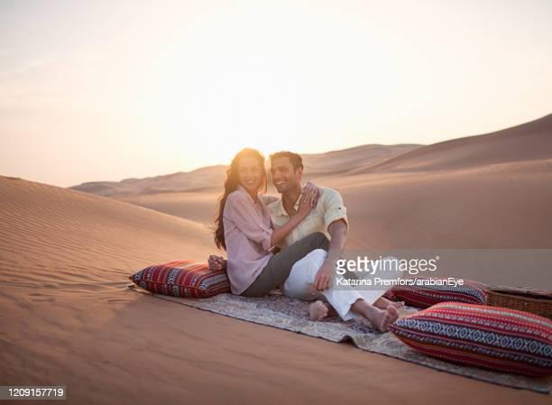couple sitting on blanket on desert. - ras al khaimah stock pictures, royalty-free photos & images