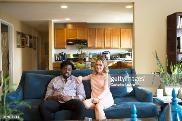 Couple sitting on blue sofa with kitchen in background