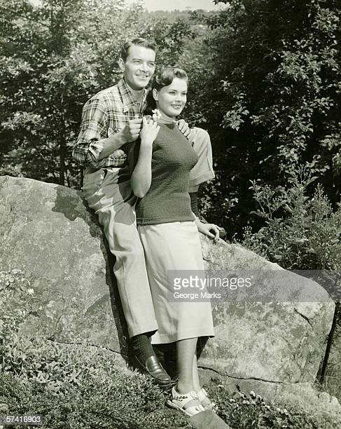 Couple sitting on boulder in park, (B&W)