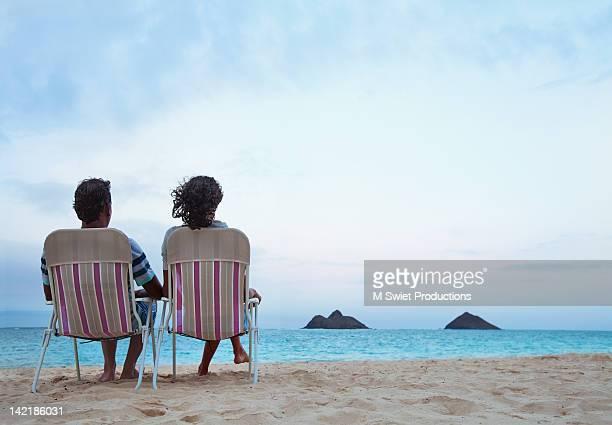 couple sitting on chair at beach in hawaii - アウトドアチェア ストックフォトと画像
