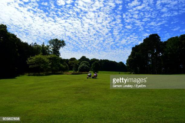 Couple Sitting On Chair At Park Against Sky