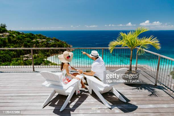 couple sitting on chairs at observation point against sea - dominica stock pictures, royalty-free photos & images