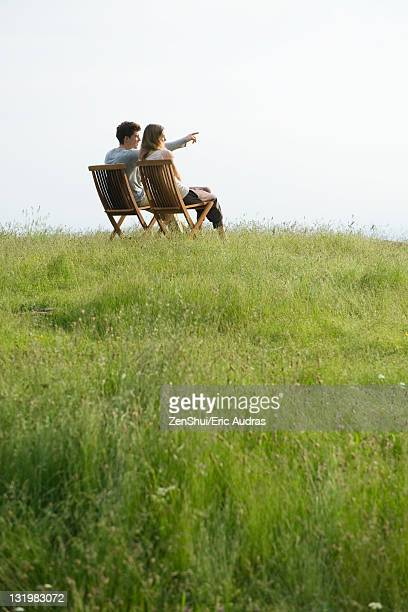 Couple sitting on chairs on top of hill looking at view, man pointing toward distance