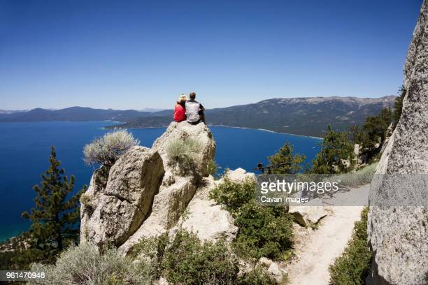Couple sitting on cliff overlooking lake against clear blue sky