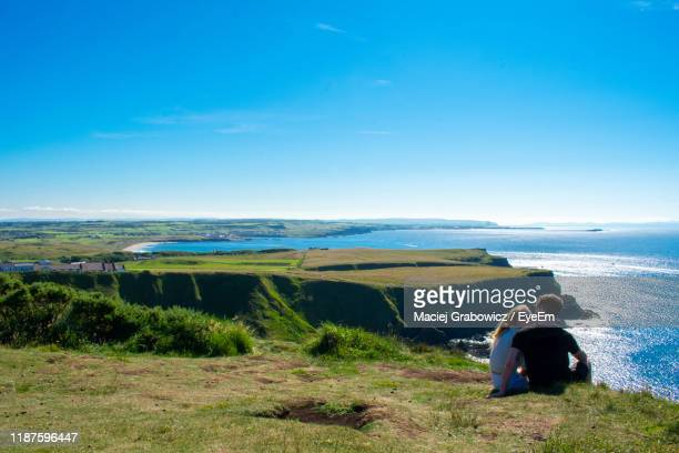 couple sitting on cliff with sea in background against blue sky - northern ireland stock pictures, royalty-free photos & images