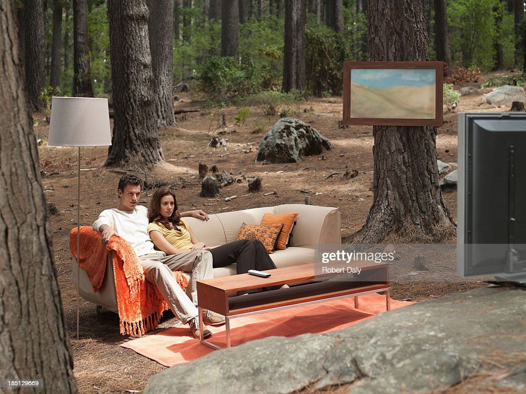 A couple sitting on coach watching television outdoors in the woods : Stock Photo