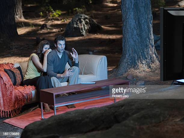a couple sitting on coach watching television outdoors in the woods - só adultos imagens e fotografias de stock