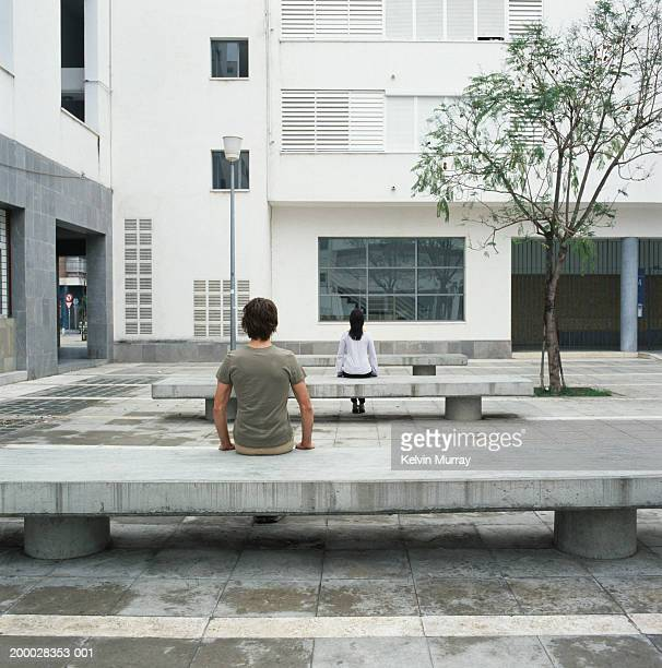 couple sitting on concrete benches outdoors, rear view - 中庭 ストックフォトと画像