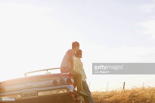 Couple sitting on convertible in countryside