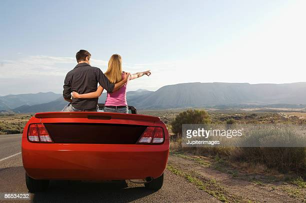 Couple sitting on convertible pointing at landscape