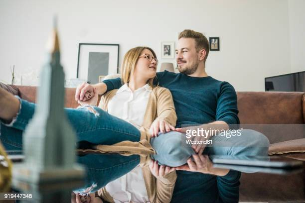 couple sitting on couch at home with model of empire state building - feet up stock pictures, royalty-free photos & images
