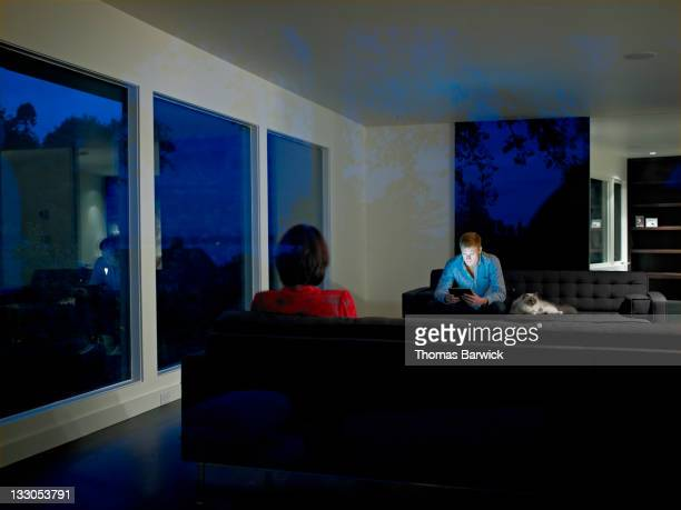 Couple sitting on couches in living room of home