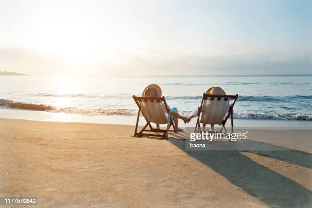 couples s'asseyant sur la présidence de plate-forme à la plage - transat photos et images de collection