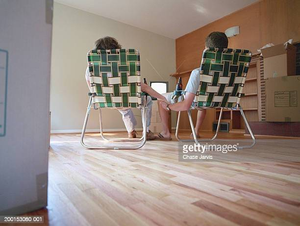 Couple sitting on deck chairs in empty room, watching TV, rear view