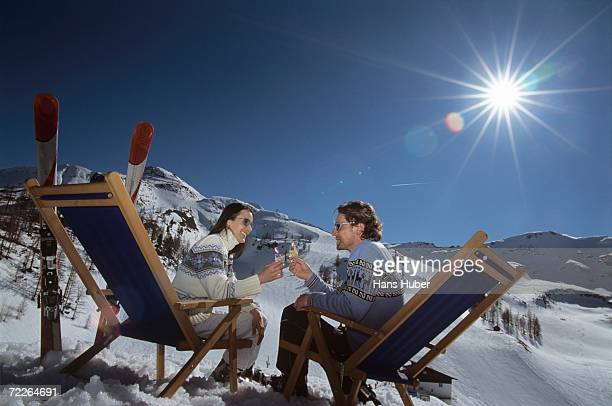 Couple sitting on deck chairs in snow, holding glasses, side view