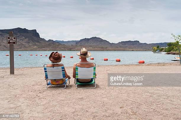 couple sitting on deck chairs, lake havasu, arizona, usa - lake havasu stock photos and pictures