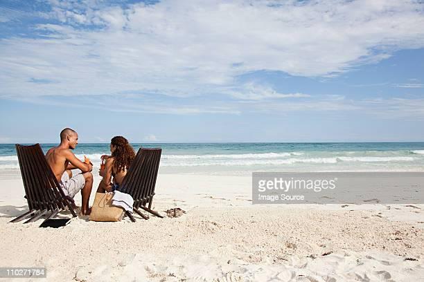 Paar sitzt auf Liegestühle am Strand