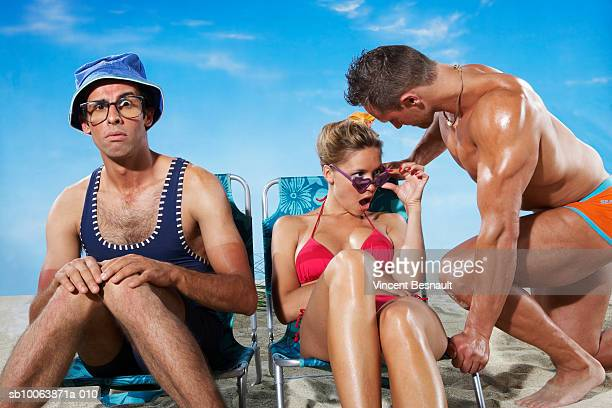 Couple sitting on deckchair, woman looking at man