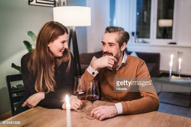 couple sitting on dining table during christmas party - candle light stock pictures, royalty-free photos & images