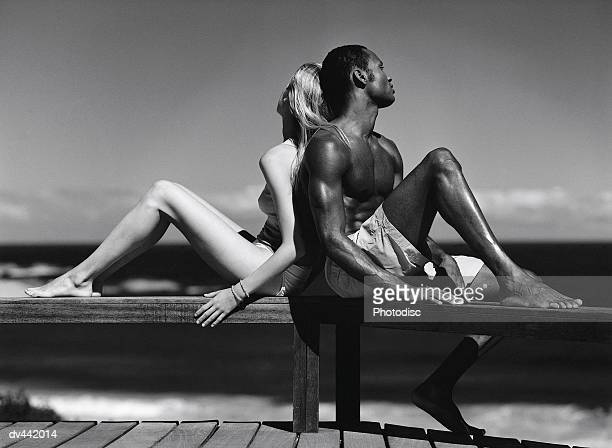Couple sitting on dock at ocean