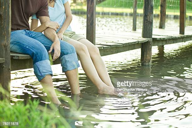 Couple sitting on dock, dangling legs in water, chest down
