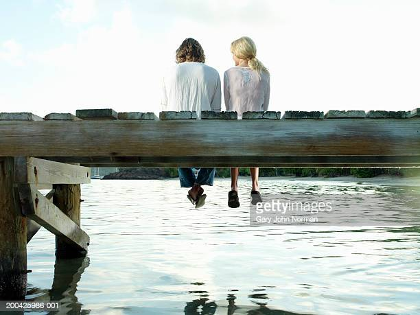 Couple sitting on dock, rear view